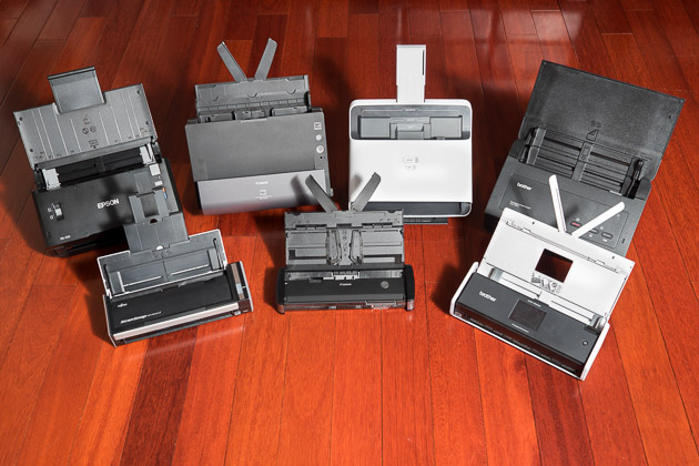 After researching nearly 100 document scanners, we tested four desktop models, (back row, l to r) the Epson DS-510, Canon C225, NeatDesk, and Brother ADS-2000, and three portable units, (front row, l to r) the Fujitsu S1300i, Canon P-215II, and Brother ADS1500W.