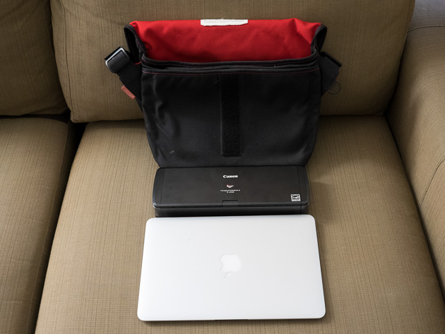 A portable document scanner like the Canon P-215II is compact enough to fit in this small shoulder bag alongside an 11-inch Macbook Air.