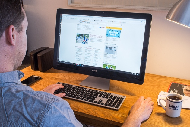 An over-the-shoulder shot of a person using the Asus Zen at a wooden desk, with an Ihop mug and cellphone at either side of the keyboard. The computer is open to the Wirecutter homepage.