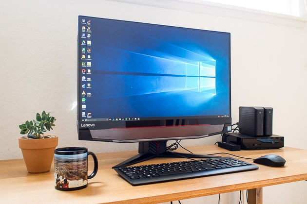 The Lenovo IdeaCentre on a wooden desk, with a potted plant and a mug next to it. Its wallpaper is blue.