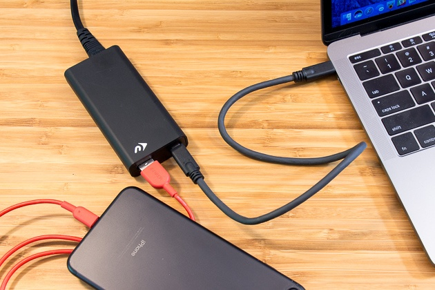 The NuPower in action, charging an open MacBook Pro (whose corner is visible in the photo) and an iPhone. The lightning cable connecting it to the iPhone is red.
