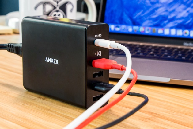 The Anker PowerPort+ 5 in action, with one USB-C cable and two USB cables connected (leaving two USB slots open). The USB-C cable is white, one USB cable is red, and another USB cable is black. A MacBook is out of focus in the background.