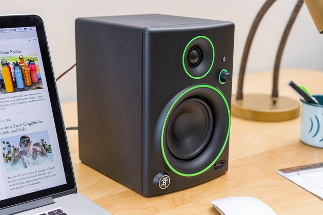 A black Mackie CR4BT computer speaker with green detail sitting next to a Macbook.