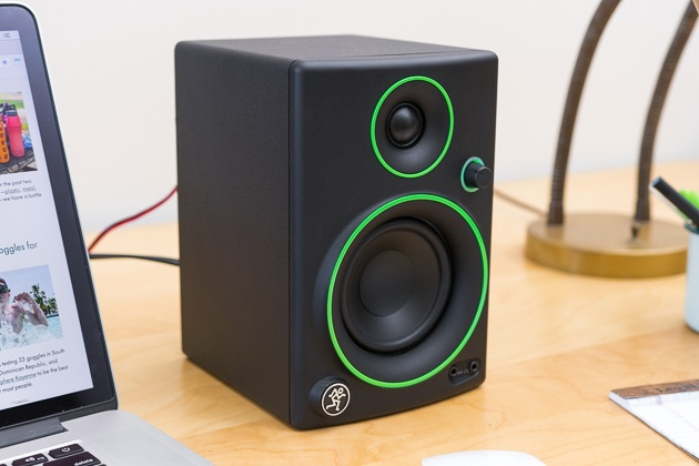 A black Mackie CR3 computer speaker with green detail sitting next to a Macbook.