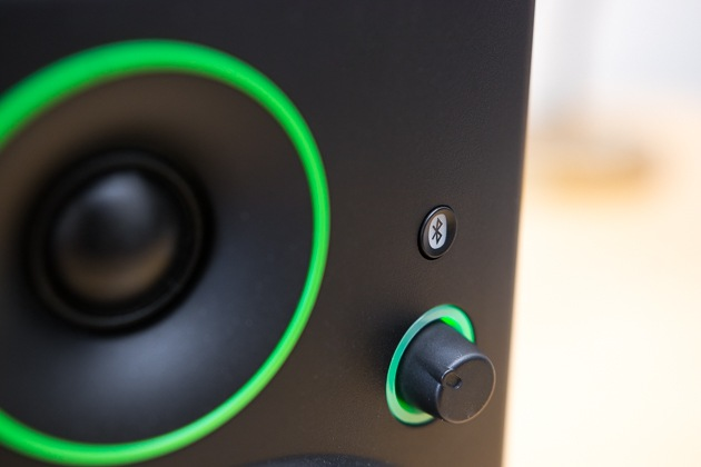 A closeup photo of the bluetooth pairing button on the front of a Mackie CR4BT computer speaker.