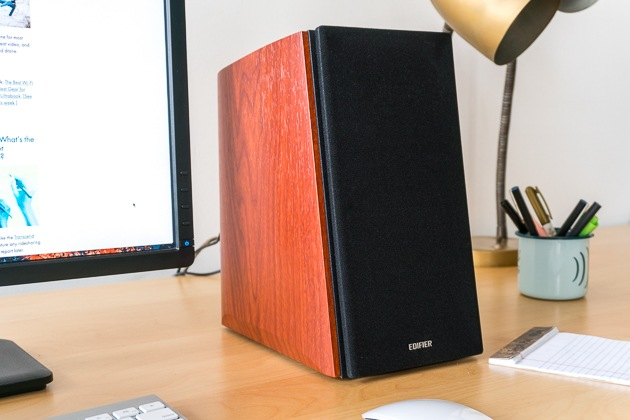A cherry wood finished Edifier R2000DB computer speaker sitting on a desk next to a computer.