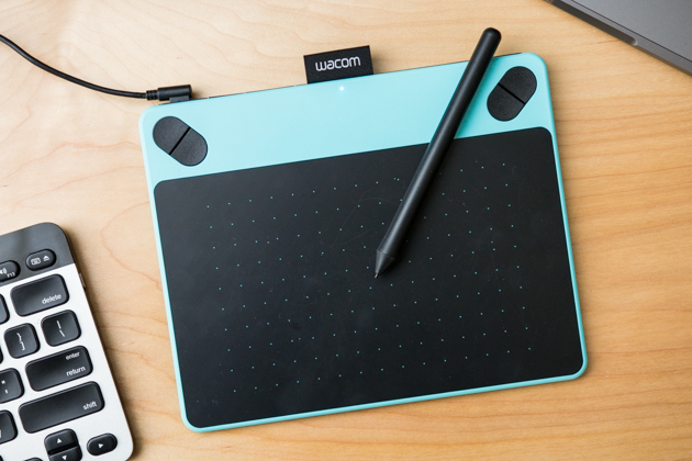 A closeup of the Wacom Intuos Draw and its pen. The tablet is light blue around its borders with a black active area printed with a blue dot grid.