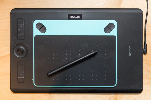 A smaller Wacom Intuos Draw sitting on top of the Intuos Pro to show the difference in size between the two.