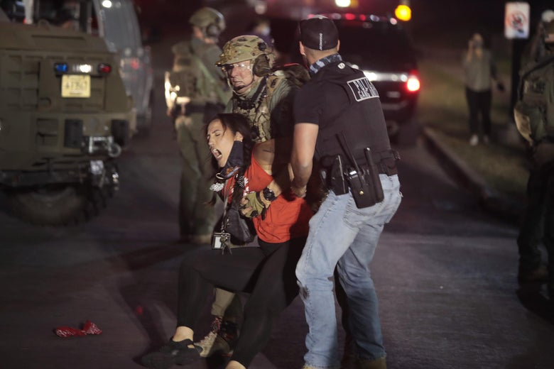 A National Guardsmen and a plainclothes law enforcement officer grasp onto a screaming woman.