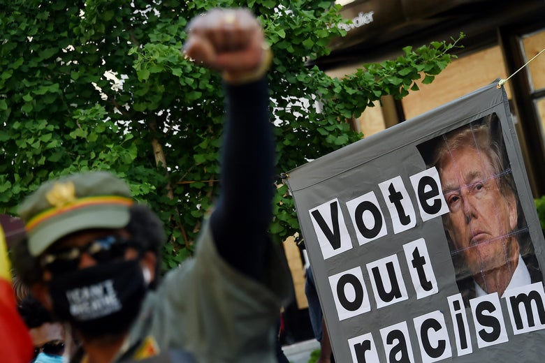 A demonstrator raises his fist in front of a sign calling to vote out racism with a picture of President Donald Trump.