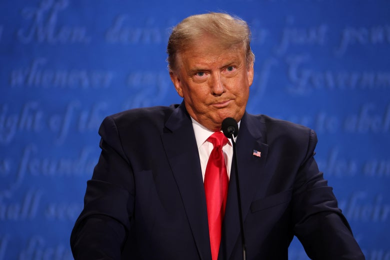 Donald Trump, standing at a lectern, makes a sour face.