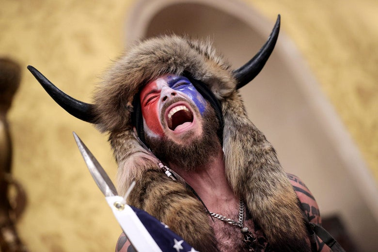 A shirtless, screaming man wearing a raccoon hat with horn screams in the Capitol.