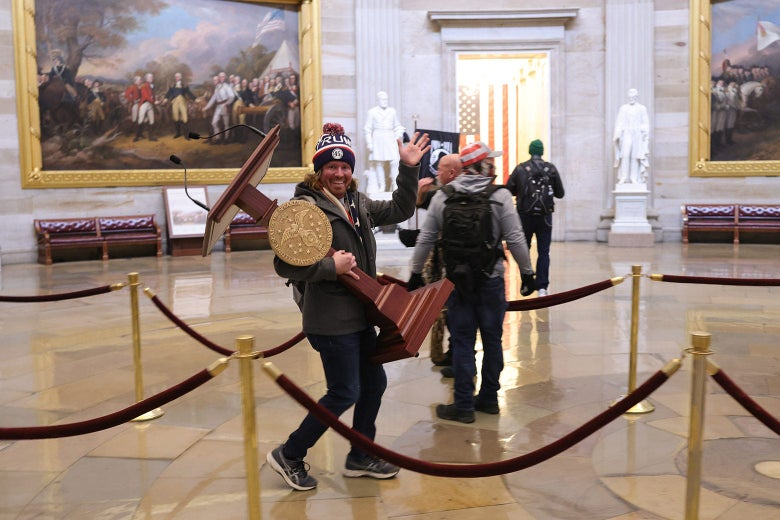 A protester in a Trump beanie smiles and waves at the camera while walking through the Capitol holding a podium for the speaker of the House.