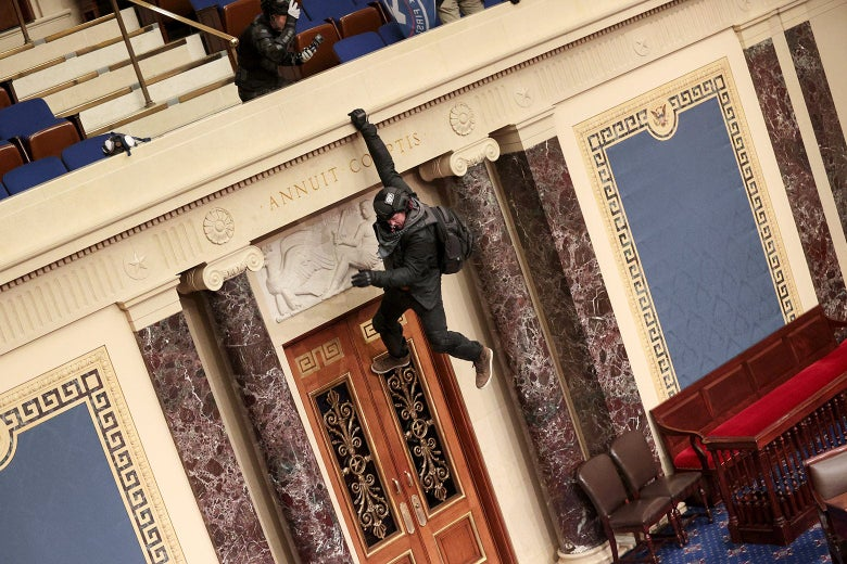 A man with a backpack swings from the Senate chamber's balcony. He is hanging on with one hand.