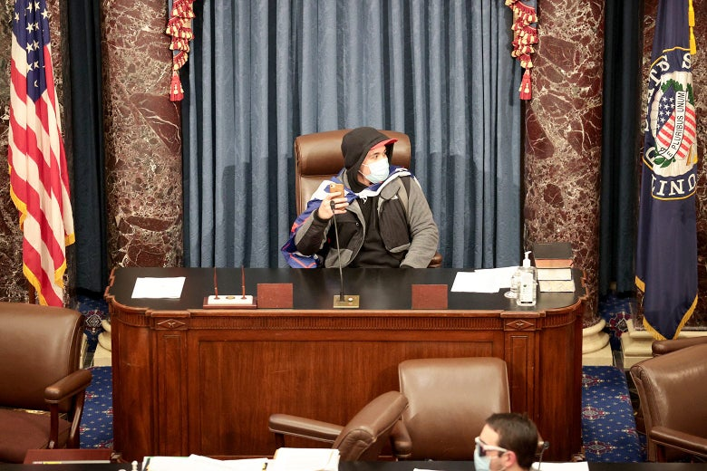 A Trump supporter wearing a surgical mask and holding an iPhone sits at a desk in the Capitol's Senate chamber.