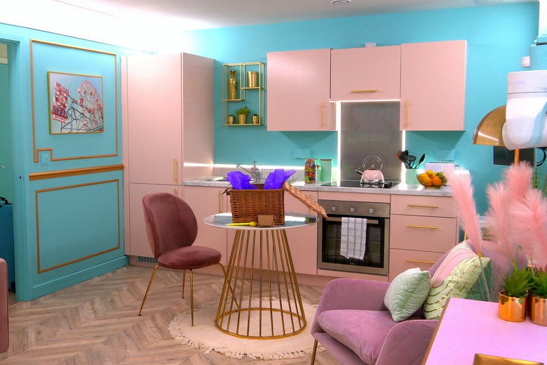 A room with turquoise blue walls and pink cabinets. There is a floral painting hanging on the wall behind a single red dining chair at a gold and white small table. In the corner is a dusty pink armchair with light green pillows. Next to it is a pink side table with two small plants sitting on top of it.