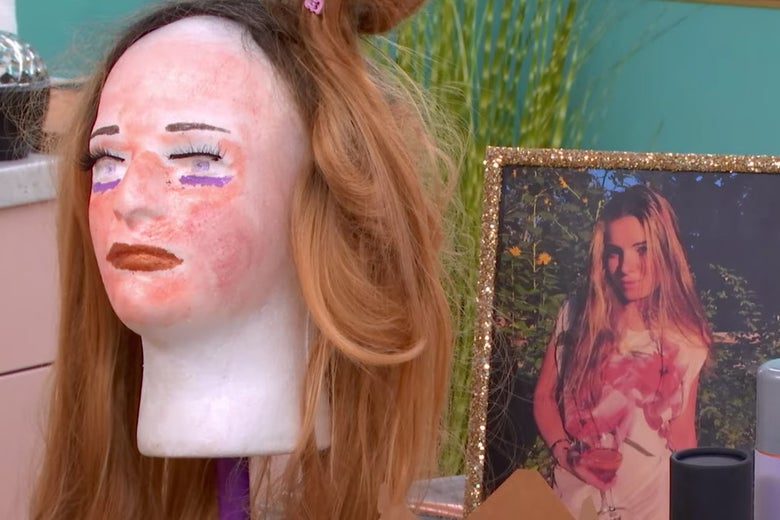 A mannequin head with a face of peach makeup and purple eyeliner wears a brown wig. Next to her is a framed photo of a girl with blonde hair holding flowers.